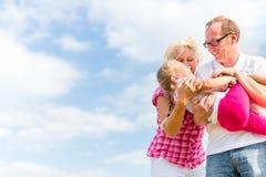 Familie, die auf Feld herumtollt Stockbilder