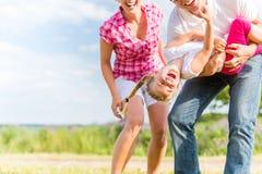 Familie, die auf Feld mit den Eltern tragen Kind herumtollt Stockfotos