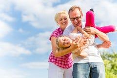 Familie, die auf Feld mit Eltern herumtollt Stockbild