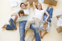 Familie, die auf Fußboden durch geöffnete Kästen im neuen Haus liegt Lizenzfreies Stockfoto