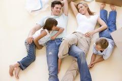 Familie, die auf Fußboden durch geöffnete Kästen im neuen Haus liegt Stockbild