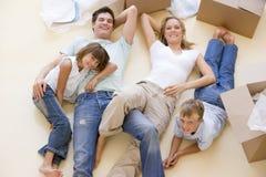 Familie, die auf Fußboden durch geöffnete Kästen im neuen Haus liegt Lizenzfreie Stockfotos