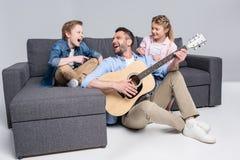 Familie, die auf Gitarre spielt und, Zeit zusammen verbringend beim Sitzen auf Sofa singt Lizenzfreies Stockfoto