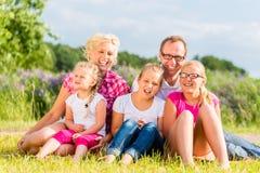 Familie, die auf Gras auf Rasen oder dem Gebiet sitzt Lizenzfreie Stockfotografie