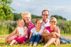 Familie, die auf Gras auf Rasen oder dem Gebiet sitzt Lizenzfreies Stockbild