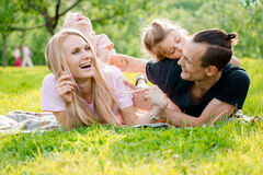 Familie, die auf Gras in der Landschaft liegt Stockbild