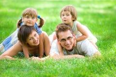 Familie, die auf Gras liegt Stockfotos