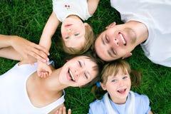 Familie, die auf Gras liegt lizenzfreie stockfotos