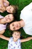Familie, die auf Gras liegt Lizenzfreie Stockfotografie