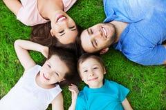 Familie, die auf Gras liegt lizenzfreies stockfoto