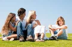 Familie, die auf Gras sich entspannt lizenzfreie stockfotografie