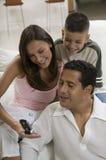 Familie, die auf Handy schaut Stockbild
