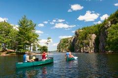 Familie, die auf Kanus auf dem See schaufelt Stockfotos