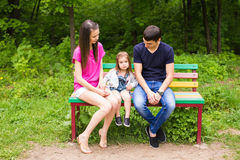 Familie, die auf Parkbank sitzt lizenzfreies stockfoto