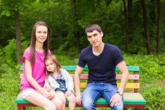 Familie, die auf Parkbank sitzt lizenzfreie stockfotografie