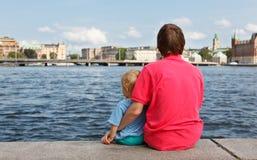 Familie, die auf Pier sitzt Stockbild