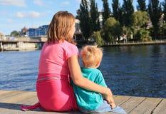 Familie, die auf Pier sitzt Lizenzfreie Stockbilder