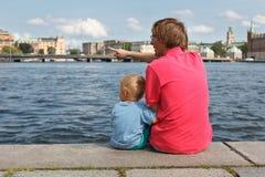 Familie, die auf Pier sitzt Lizenzfreie Stockfotos
