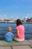Familie, die auf Pier sitzt Stockbilder