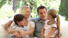 Familie, die auf Sofa At Home Talking sitzt stock footage