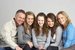 Familie, die auf Sofa sitzt stockfotografie