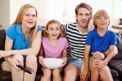 Familie, die auf Sofa Watching Soccer Together sitzt lizenzfreie stockbilder