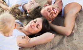 Familie, die auf Strand, Draufsicht liegt Stockfotos