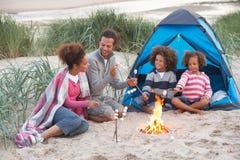 Familie, die auf Strand kampiert und Eibische röstet Lizenzfreie Stockfotografie