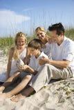 Familie, die auf Strand sitzt. Lizenzfreie Stockbilder