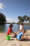 Familie, die auf Strand spielt Stockfoto