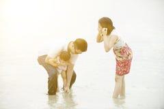 Familie, die auf Strand spielt Stockbild