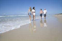 Familie, die auf Strandholdinghände geht Lizenzfreie Stockfotografie