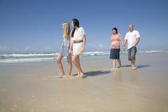 Familie, die auf Strandholdinghände geht Stockbilder