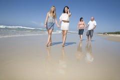 Familie, die auf Strandholdinghände geht Stockfotos