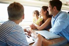 Familie, die auf Zug-Reise sich entspannt stockfotos