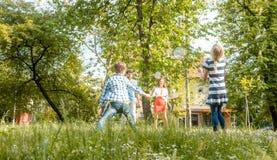 Familie, die Badminton auf einer Wiese im Sommer spielt stockfotografie