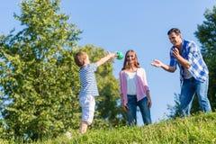 Familie, die Ball auf Sommerwiese spielt Stockbilder