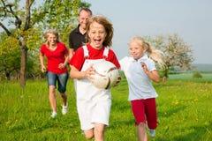 Familie, die Ballspiele spielt Lizenzfreies Stockfoto