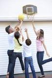 Familie, die Basketball außerhalb der Garage spielt Stockbild