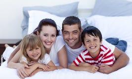 Familie die in bed samen ligt Stock Afbeeldingen