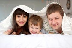 Familie die in bed samen rusten Stock Afbeelding