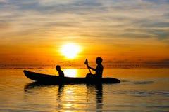 Familie, die bei Sonnenuntergang Kayak fährt Stockfotografie