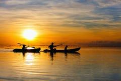 Familie, die bei Sonnenuntergang Kayak fährt Stockbilder
