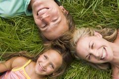 Familie, die beim Graslächeln liegt Lizenzfreie Stockfotografie