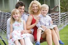 Familie, die beim Hängemattenlächeln sitzt Stockfotos