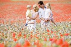 Familie, die beim Mohnblumefeldlächeln steht Lizenzfreies Stockfoto