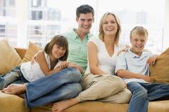 Familie, die beim Wohnzimmerlächeln sitzt stockfotos