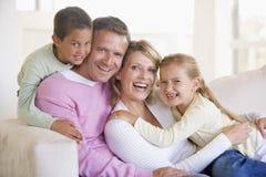 Familie, die beim Wohnzimmerlächeln sitzt Lizenzfreie Stockbilder