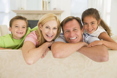 Familie, die beim Wohnzimmerlächeln sitzt lizenzfreie stockfotos