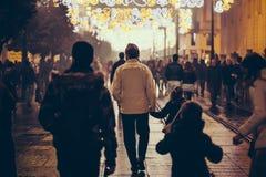 Familie die bij Kerstmisnacht lopen Stock Foto's